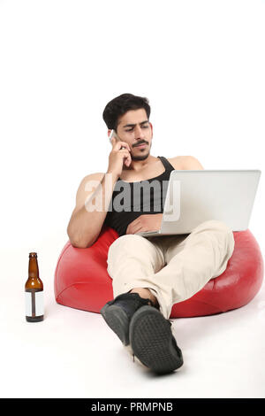 Young boy with laptop talking on mobile phone. boy sitting on bean bag couch with juice bottle. Isolated on white background. - Stock Photo