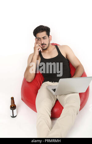 Picture of young boy thinking with laptop and beer bottle. Isolated on white background. - Stock Photo