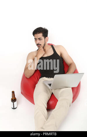 Picture of boy sitting on the bean bag couch. Young boy thinking with laptop and beer bottle. Isolated on white background. - Stock Photo