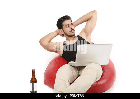 Picture of boy sitting on the bean bag couch. Young boy relaxing with laptop and beer bottle. Isolated on white background. - Stock Photo