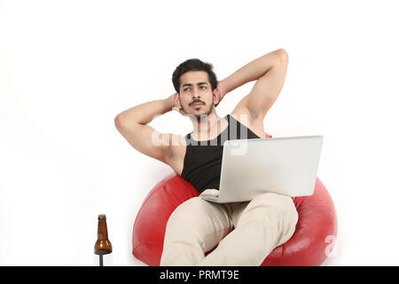 Picture of handsome boy thinking with laptop and juice bottle. Isolated on white background. - Stock Photo