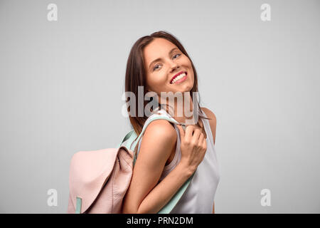 Portrait of energetic teenager girl isolated on gray background pulling forward straps of hipster backpack, laughing happily as if anticipating friend - Stock Photo
