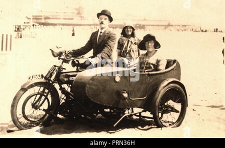 Family of three pose for photograph, sat on a 1920 BSA side valve single motorcycle & sidecar combination on the beach at the seaside in the 1920s - Stock Photo