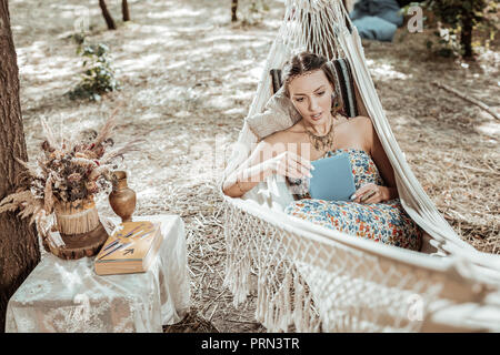 Beautiful young woman reading something in tablet - Stock Photo