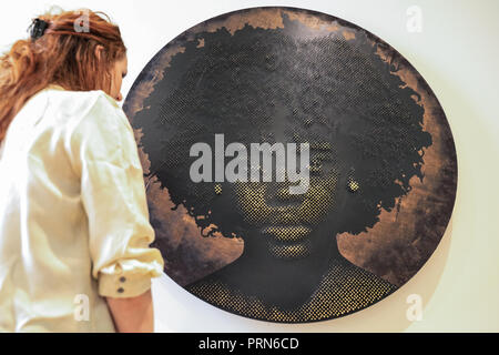 London, UK, 3rd Oct 2018. An assistant poses with a piece by Alexis Peskine. 1-54 Contemporary African Art Fair, showing art from Africa and its diaspora, launches its sixth London edition at Somerset House with an installation by Sudanese artist Ibrahim El-Salahi in the Edmond J. Safra Fountain Court; an exhibition of new and rarely seen works from internationally renowned South African artist Athi-Patra Ruga in the Terrace Rooms; and 43 international galleries from 17 countries throughout Somerset House. - Stock Photo