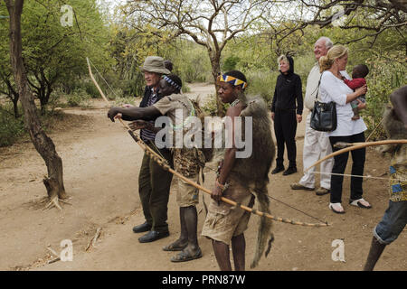 May 23, 2017 - Lake Eyasi, Ngorongoro district, Tanzania - American tourists visit one of the aproximately thirty Hadza camps. A white woman holds a black baby in her hands, while her husband tries to shoot an arrow on a distant tree. Each tourist group must pay a $20 fee for each visit. Small pocket money from tourism has become the main source of income for the Hadza people.The Hadza are one of the last remaining societies, which remain in the world, that survive purely from hunting and gathering. Very little has changed in the way the Hadza live their lives. But it has become increasingly h - Stock Photo