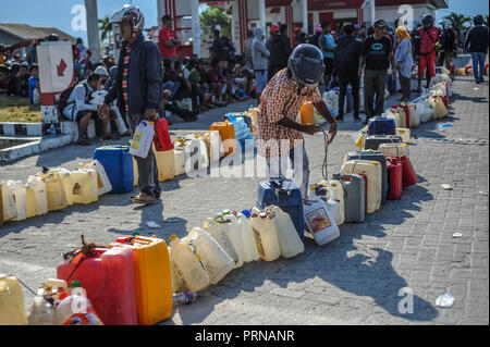 Palu, Central Sulawesi, Indonesia. 3rd Oct, 2018. Residents seen lining up to buy fuel in the Tondo gas station, They have to queue for up to 12 hours to get it.A deadly earthquake measuring 7.7 magnitude and the tsunami wave caused by it has destroyed the city of Palu and much of the area in Central Sulawesi. According to the officials, death toll from devastating quake and tsunami rises to 1,347, around 800 people in hospitals are seriously injured and some 62,000 people have been displaced in 24 camps around the region. Credit: Hariandi Hafid/SOPA Images/ZUMA Wire/Alamy Live News - Stock Photo