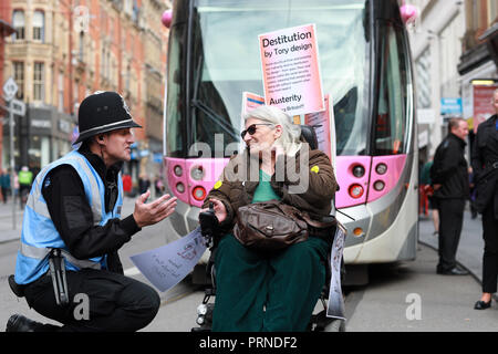 Birmingham, UK. 3rd October, 2018. Police try to negotiate with disabled rights protestors who blocked the main tramline out of Birmingham New Street station for about an hour yesterday afternoon  .They were demonstrating against the Conservative Government implimentation of austerity cuts . Research by the Joseph Rowntree Foundation found around 650,000 people with mental and physical health problems were officially destitute in the UK last year. Credit: Paul Pickard/Alamy Live News - Stock Photo