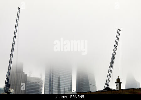 London, UK. 4th October, 2018. Cranes in front of a blanket of fog that obscures the skyline of the city of London. Credit: Kevin Frost/Alamy Live News - Stock Photo