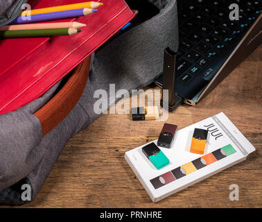 JUULpods and dispenser charging in laptop computer - Stock Photo
