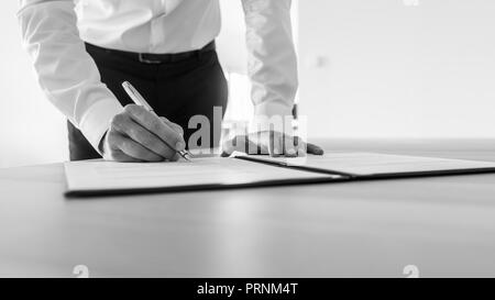 Greyscale image of businessman standing at his desk signing contract or legal document. - Stock Photo