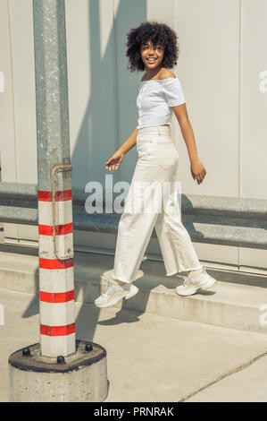 happy young african american woman walking and smiling on street - Stock Photo