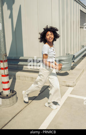beautiful smiling young african american woman walking on street - Stock Photo