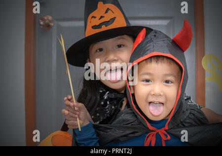 Happy boy devil smile and cute little witch, halloween concept - Stock Photo