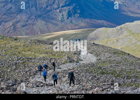 Walkers descending from on the summit of Scafell Pike, highest Mountain in England - Stock Photo