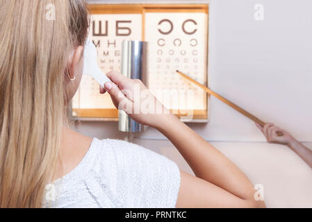 A young girl checks her eyesight in the hospital. - Stock Photo