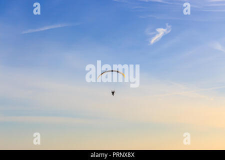 Single Powered paraglider with red and yellow canopy in blue sky and soft wispy clouds - Stock Photo