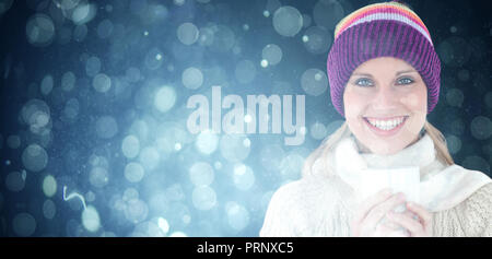 Composite image of glowing woman wearing a white pullover and a colourful hat against white backgrou - Stock Photo