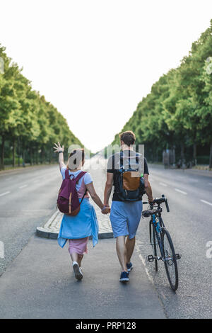 rear view of woman with backpack pointing by hand to boyfriend walking near with bicycle - Stock Photo