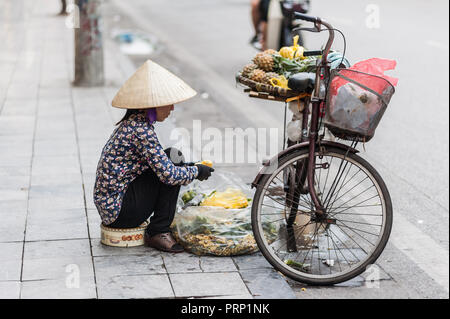 Street vendor with a bicycle on the streets of Hanoi, Vietnam. Selling pineapples in the middle of busy traffic in the capital city. - Stock Photo