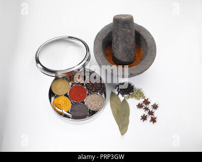 Stone grinder and pestle with stainless masala dabba on a white background - Stock Photo
