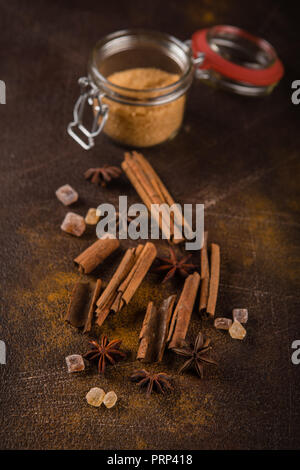 Cinnamon sticks, anise sprouts and caramelized sugar on a dark background. View from above. Close-up. - Stock Photo