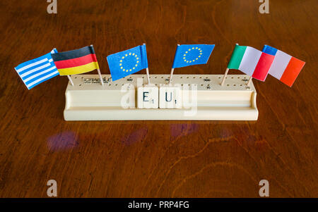 Scrabble letters spelling EU in Scrabble tray with European Union, German, Greek French and Italian flags on mahogany background - Stock Photo