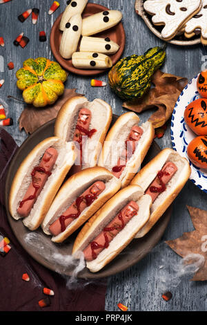 high angle view of an assortment of funny halloween food, such as hotdogs in the shape of bloody fingers, tangerines as carved pumpkins with funny fac - Stock Photo