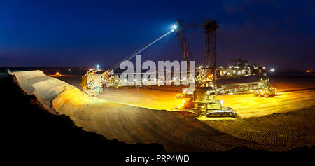 Panorama of a lignite surface mine with a giant bucket-wheel excavator, one of the worlds largest moving land vehicles with night blue sky. - Stock Photo