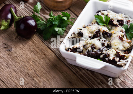 Stuffed eggplants with sun dried tomatoes and mozzarella cheese in ceramic dish on rustic wooden table - Stock Photo
