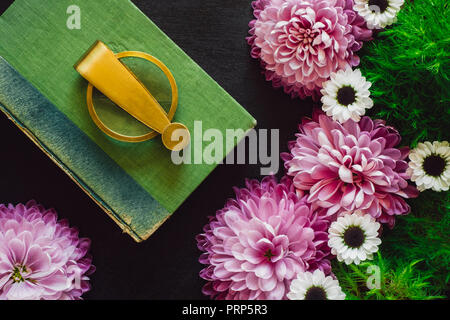 Antique Book and Magnifying Glass with Pink and White Mums on Black Table - Stock Photo