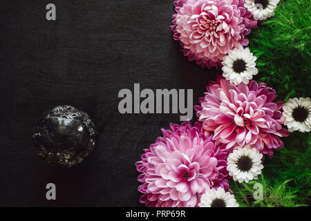 Black Tourmaline Sphere with Pink and White Mums on Black Table - Stock Photo