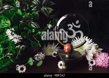 Red Jasper Sphere on Om Altar with Mixed Flowers and Foliage - Stock Photo