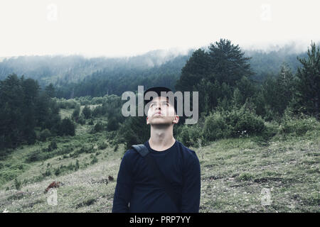 young hiker looking up to sky in front of forest and fog