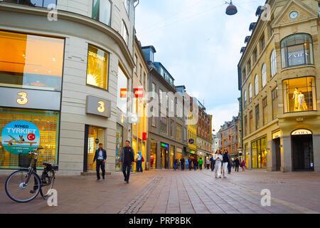 COPENHAGEN, DENMARK - JUNE 16, 2018: People walk by the Stroget street - the main shopping street of Copenhagen. - Stock Photo