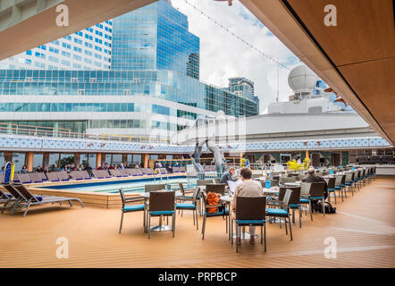 Lido Deck swimming pool under open retractable Magradome roof. The Volendam, Holland America R Class cruise ship. Docked at Port Of Vancouver, British Columbia, Canada. Downtown Vancouver buildings in background. - Stock Photo