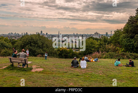 People have fun and enjoy the London skyline from the top of Parliament Hill, in Hampstead Heath, in north-west London. - Stock Photo