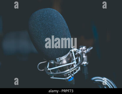 closeup photo of a black microphone in a garage studio - Stock Photo