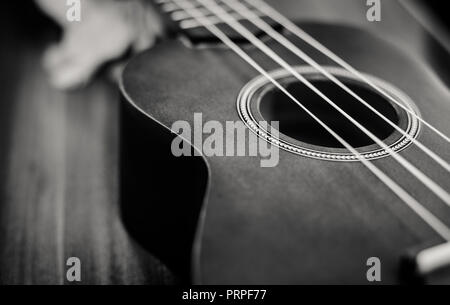 closeup photo of a ukulele against a brown background - Stock Photo