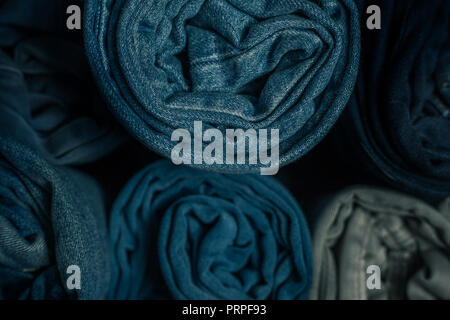 closeup photo of several rolled pairs of jeans - Stock Photo