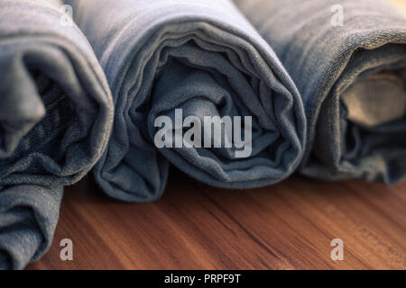 closeup photo of blue jeans rolled on a wooden table - Stock Photo