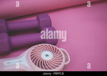 photo of two purple weights and a portable fan on a pink yoga mat - Stock Photo
