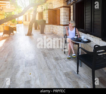 A young woman sits at a table in a cafe on the street and enjoys her morning coffee. - Stock Photo