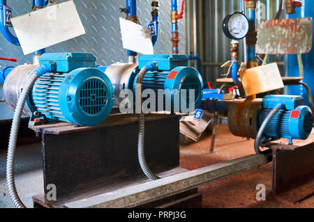 Old blue electric motor to the pump, valve and pressure gauge on the pipeline. Industrial background. - Stock Photo