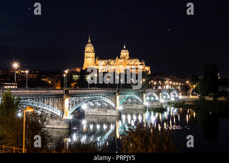 Night view of Salamanca Old and New Cathedrals from Enrique Esteban Bridge over Tormes River, Community of Castile and León, Spain.  Declared a UNESCO - Stock Photo