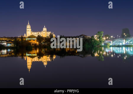 Night view of Salamanca Old and New Cathedrals from Enrique Esteban Bridge over Tormes River, Community of Castile and Leon, Spain. - Stock Photo