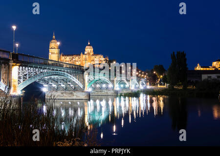 Night view of Salamanca Old and New Cathedrals from Enrique Esteban Bridge over Tormes River, Community of Castile and León, Spain. - Stock Photo