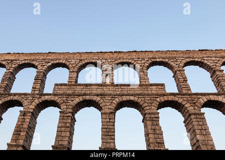 Upper side of roman aqueduct, with detail of Virgin of the Aqueduct, located in the central niche of the monument has since the Plaza del Azoguejo, Se - Stock Photo