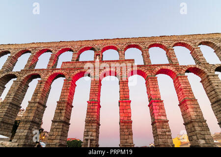 Roman aqueduct of Segovia at sunset, with detail of Virgin of the Aqueduct, located in the central niche of the monument has since the Plaza del Azogu - Stock Photo