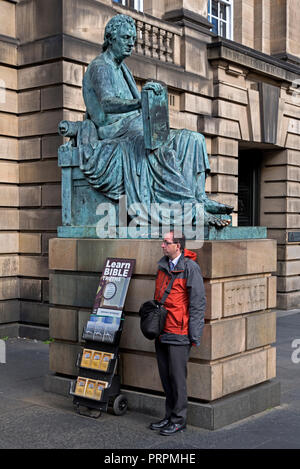A member of Jehovah's Witnesses standing next to the statue of the Scottish Philosopher David Hume on the Royal Mile in Edinburgh, Scotland, Uk. - Stock Photo